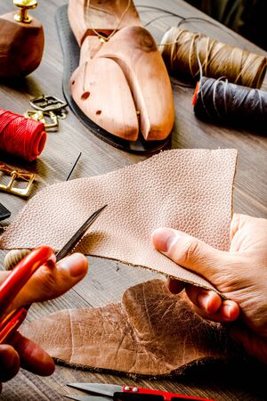 cobbler tools in workshop dark background close up Фото со стока