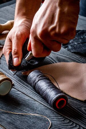 work in leather shop on dark wooden background close up