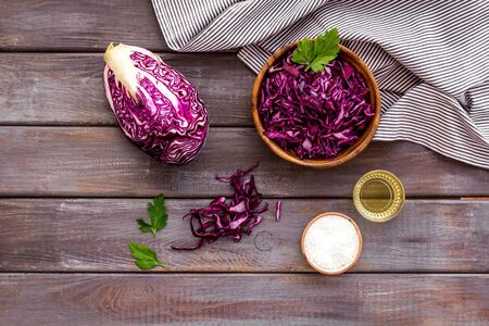 Red cabbage - cut head and sliced - on wooden kitchen table top view.