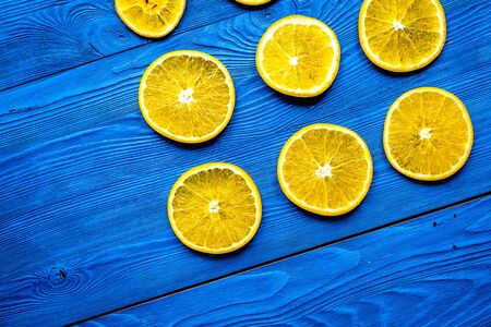 Cut orange fruits on blue wooden background top view mockup Stock Photo