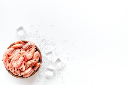 Shrimps in bowl near ice on white background top view copy space. Seafood