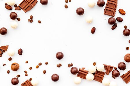 Candy background with chocolate on white table top view frame. Sweets desserts concept. Space for text