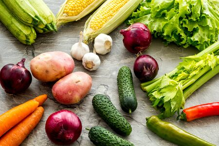 Fresh vegetables still life. Potato, cucumber, beet carrot, greenery on grey background Stok Fotoğraf