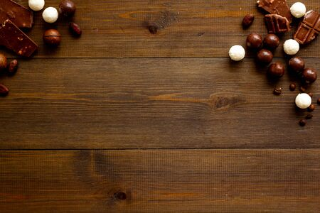 Sweets background with chocolate praline balls on wooden desk top-down frame copy space