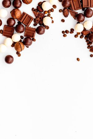 Chocolate background on white table top-down frame. Sweet desserts concept. Copy space