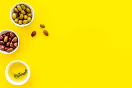 Green and res olives with oil on yellow background. Top view