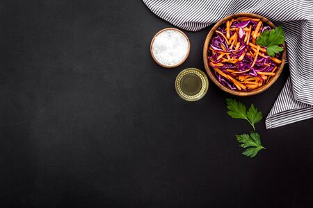 Healthy vegan salad with red cabbage on black kitchen table top view copy space