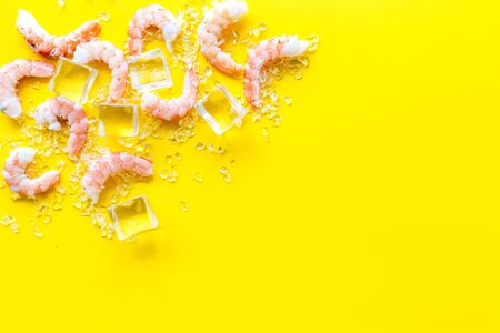 Shrimps - peeled, with ice - on yellow background frame copy space