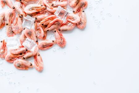 Shrimps - frozen, with ice, at shell - on white backgroud frame copy space