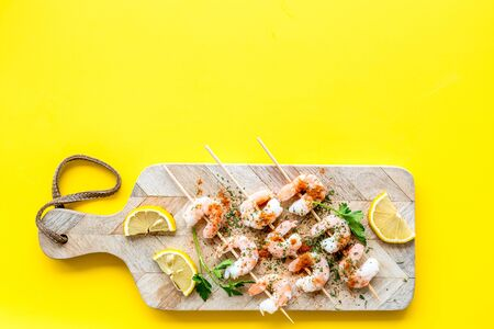 Shrimp skewers - seafood - on yellow table top view copy space