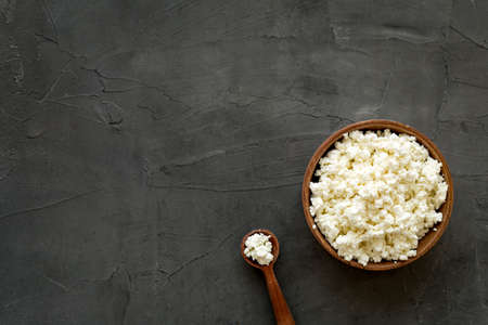 Cottage cheese in wooden bowl on white table top view copy space