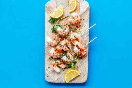 Shrimp skewers - appetizer in mediterranean kitchen - on blue table top view