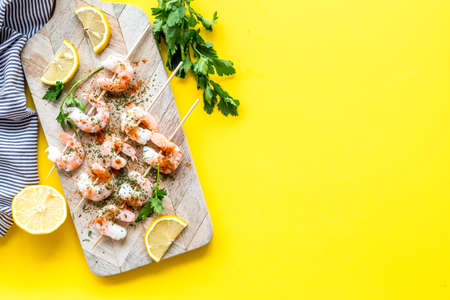 Shrimp skewers - appetizer in mediterranean kitchen - on yellow table top view copy space
