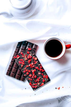 Early breakfast in silence with milk and strawberry chocolate bar and tea in red mug view from above