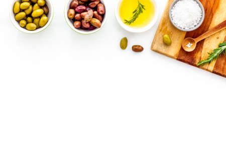 Green and black olives, olive oil in bowls on cutting board top-down copy space. Reklamní fotografie