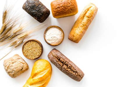 Top view of different loaves of bread and wheat ears.