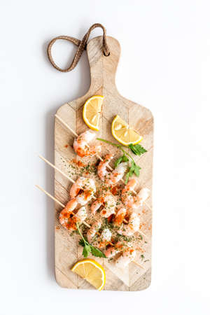 Shrimp skewers - seafood snack - on cutting bioard on white table top view.