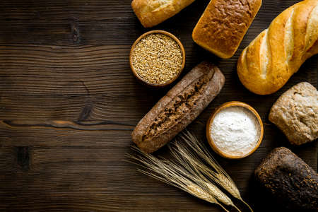 Different kinds of fresh bread on kitchen table top view.
