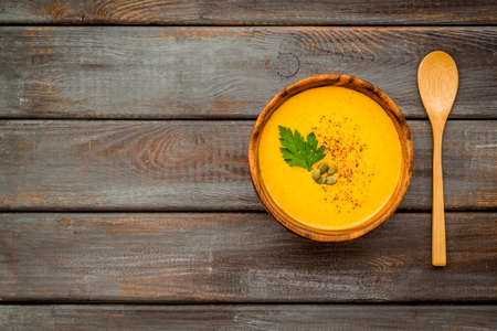 Pumpkin cream soup on wooden table top view. Autumn meal.