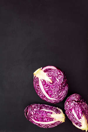 Red cabbage on black table top down.