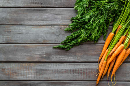 Bunch of fresh carrots with green tops form above.