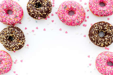 Colorful donuts pattern top view on white background.  스톡 콘텐츠