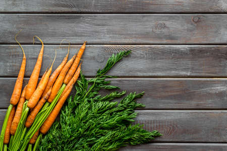 Carrot - fresh, with green tops - on wooden table top view.