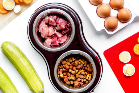 petfood set with vegetables and eggs on kitchen table background top view