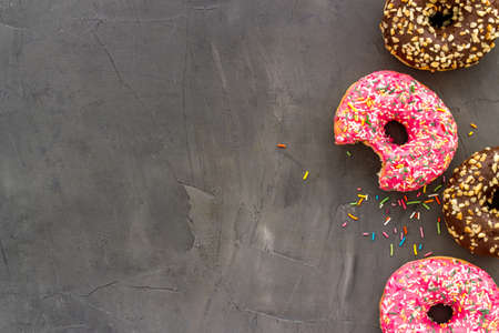 Colorful donuts pink and chocolate icing. Flat lay of bakery, above view