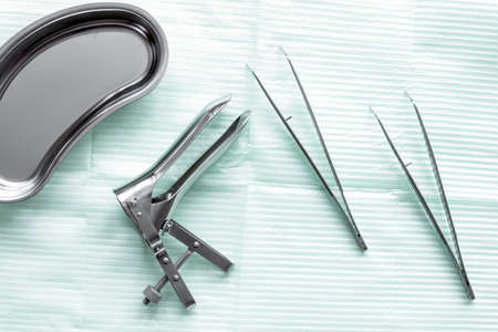 instruments of gynecologist on green background top view