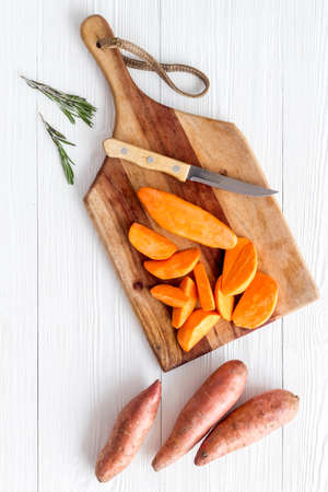 Sweet potato - sliced yams organic vegetables on cutting board, view from above Archivio Fotografico