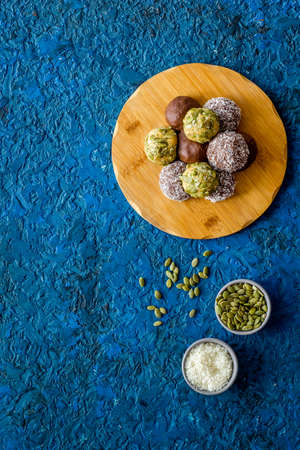 Flat lay of raw protein energy balls with nuts and cacao, top view