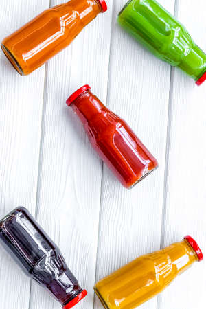 fresh organic juices in bottles for fitness diet on white wooden background top view mock-up
