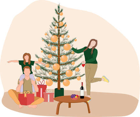The family decorates the Christmas tree. A young man with a daughter on his shoulders sits with a gift. Mother hangs toys on the Christmas tree. Family card for new year holidays
