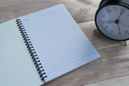 Notebook and clock with wooden floor Stock Photo