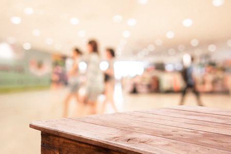 wood floor background: Shopping mall blurred background with wooden table floor