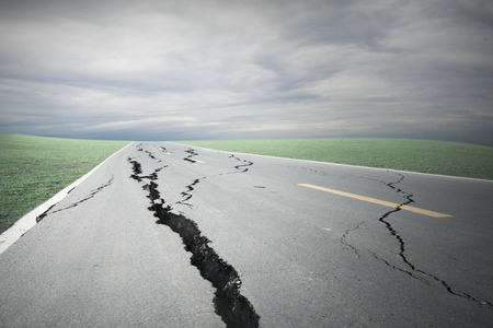 Asphalt road cracks and collapsed with storm cloud Stock Photo