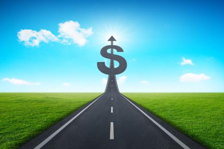 prosperidad: La carretera de asfalto en dirección a un signo de dólar con el prado verde y azul cielo