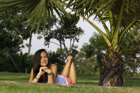 sleepiness: Young happy woman resting laying on grass in the park. Stock Photo