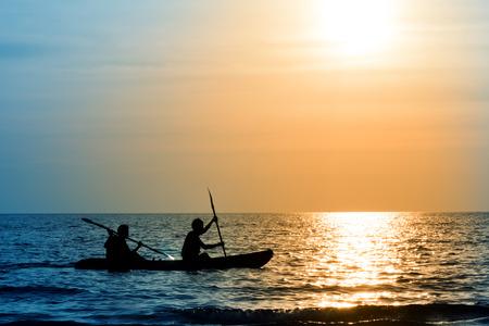 Het silhouet van de roeiboot met 2 roeiers op de achtergrond van de zonsondergang