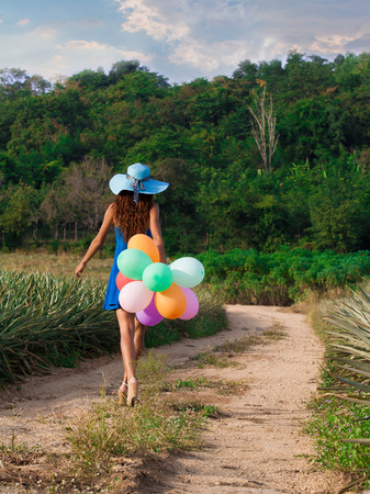 Slim beautiful girl in hat with balloons is going along a dusty road. Vintage style photo