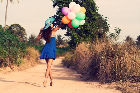 mujer sola: Hermosa chica delgada en el sombrero con globos va por un camino polvoriento. Estilo vintage