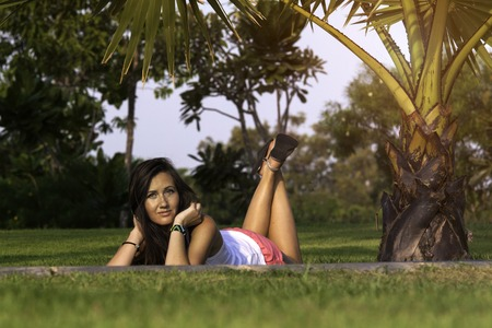 daydream: Young happy woman resting laying on grass in the park. Stock Photo