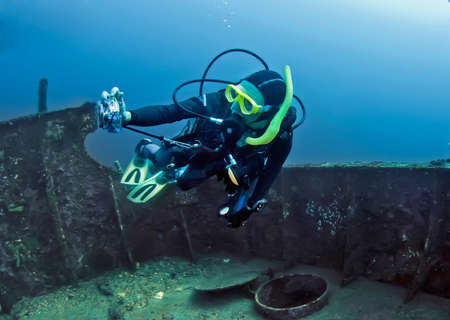 Woman underwater photographer taking images of the wreck. Philippines. Stock Photo