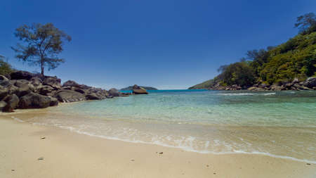 Lagoon with a wild beach - white untouched sand, clear turquoise water, blue cloudless sky on the shore - boulders of unusual shape.