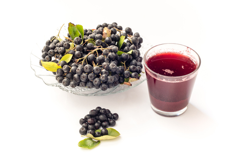 Fresh juice of black chokeberry (Aronia melanocarpa) in glass and beries in pot, isolated on white background