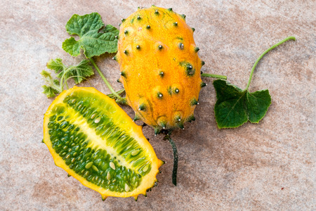 two fresh ripe kiwano with vine and leaves, Cucumis metuliferus, on ceramic background Stock Photo