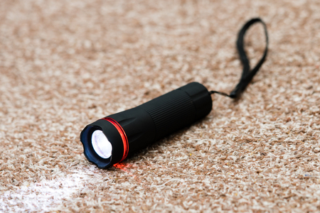 Black led flashlight with beam of light on textile background Reklamní fotografie - 98611169