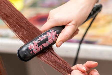 Closeup of hairdresser hands with styling iron straightening woman hair in salon. Hair care in the beauty salon.