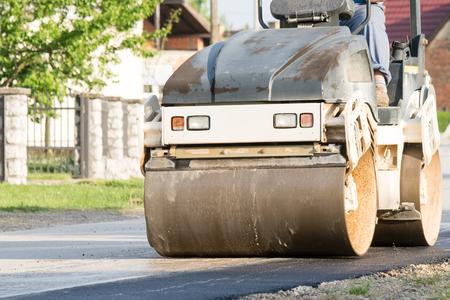 Road repair with asphalt compactor roller machine.